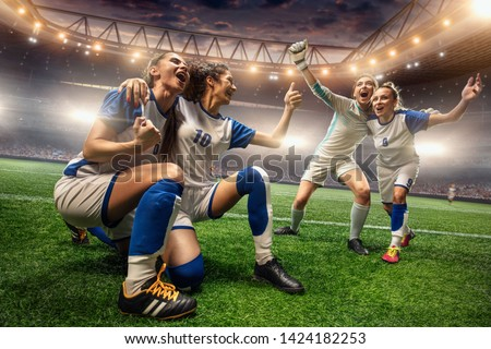 Happy Female Soccer players on a professional soccer stadium. Girls Team emotionally celebrates victory #1424182253
