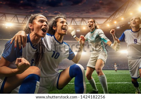 Happy Female Soccer players on a professional soccer stadium. Girls Team emotionally celebrates victory #1424182256