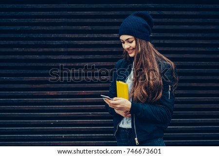 Happy female student enjoying recreation at urban setting with modern device and good mood.Young woman sending funny messages via application on cellphone during walk next to wall with promotional #746673601