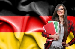 Happy female student holdimg books against national flag of Germany