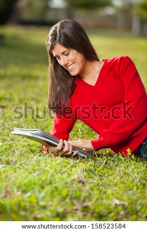 Happy female student reading book while relaxing on grass at college campus