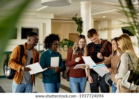 Happy female student showing test results to her friends while standing in a lobby.