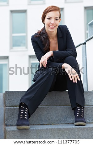 Happy female student sitting on stairs in the city - stock photo