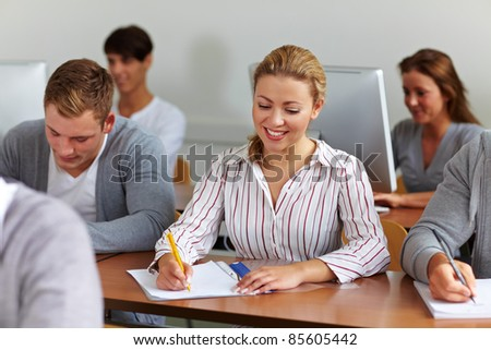 Happy female student taking notes in university class
