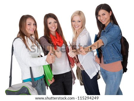 Happy female students are showing a thumbs up isolated on white
