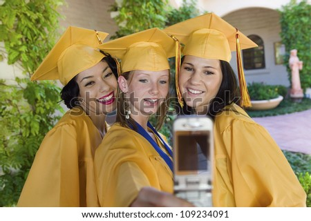 Happy female students self photographing in graduation gown