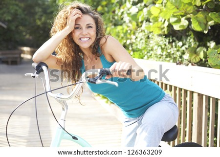 Happy Female Taking A Break On Boardwalk With Bicycle