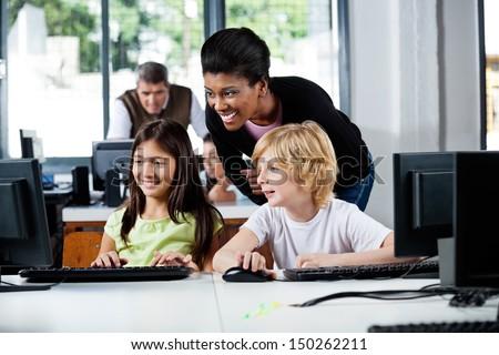 Happy female teacher assisting schoolchildren in using computer at school