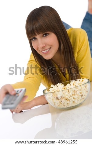 Happy female teenager watching television holding remote control, eating popcorn