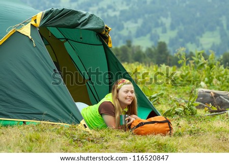 Happy female tourist drinking tea in front camp tent