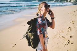 Happy female tourist in sunglasses and ravel rucksack on back talking in roaming on smartphone strolling along sandy beach.Cheerful hiker with backpack laughing while calling to friend on telephone