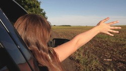 happy female traveler rides car along a country road. hand from the car window catches wind. Girl with long hair is sitting in front seat of car, stretching her arm out window and catching glare sun
