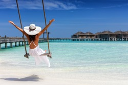 Happy female traveller is enjoying her summer vacation on a swing at a tropical beach