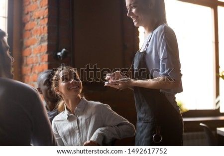 Happy female waitress holding notepad taking order serving clients in cafe pub restaurant, polite serving staff worker talking to guests diverse friends group choose food and drinks, customer service