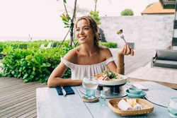 Happy female with toothy smile and dimples sitting at served table and enjoying tasty food while spending time in outdoor cafe