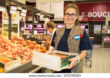Happy female worker in a supermarket holding a large wooden tray of fresh produce in her hands #509298085
