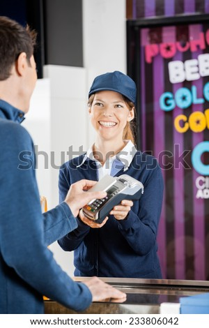 Happy female worker taking payment from man through NFC technology at cinema concession stand
