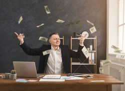 Happy financier man sitting in office and holding dollars. Man throwing out money, copy space