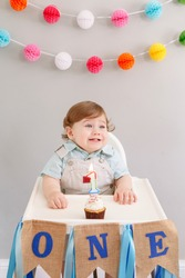 Happy first birthday cake smash. Happy smiling cute Caucasian baby boy celebrating his first birthday at home. Child kid toddler sitting in high chair eating tasty cupcake dessert with lit candle.