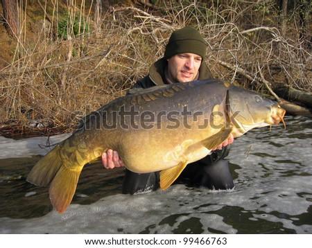 Happy  fisherman holding a giant mirror carp