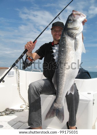 Happy  fisherman holding a sea bass