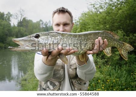 happy fisherman presents big pike, caught big fish