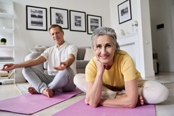 Happy fit middle aged woman exercising with husband at home,portrait.Smiling healthy old senior 60s couple meditating,doing yoga together at home,enjoying fitness activity posing on mats in apartment.