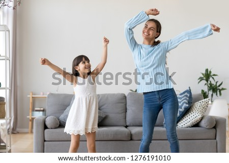 Happy fit sporty mother or baby sitter and funny active child daughter having fun dancing together at home, smiling mom and kid girl enjoy moving to music raising hands standing in living room Stockfoto ©