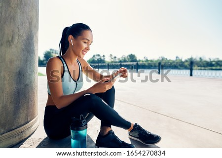 Happy fit woman holding smartphone and counts calories in sport app after running.  Sport, break concept  Сток-фото ©