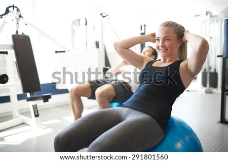 Happy Fit Young Woman Doing Sit-ups Workout on Exercise Ball While Smiling Into Distance Inside the Gym
