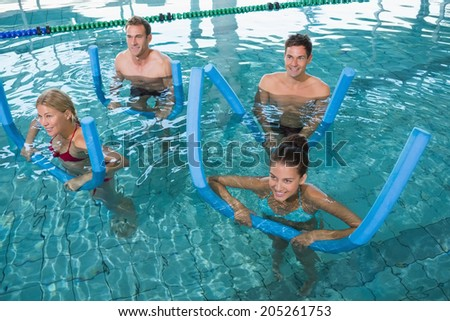 Happy fitness class doing aqua aerobics with foam rollers in swimming pool at the leisure centre