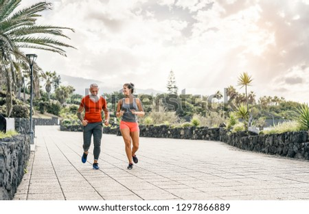 Happy fitness couple running outdoor - Fit joggers friends training outside - People, fitness lifestyle, healthy and jogging concept #1297866889