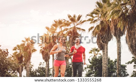 Happy fitness friends running at sunset outdoor - Couple of joggers training at evening time - People jogging, healthy, fit and sport lifestyle concept  #1333555268