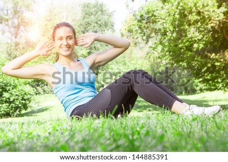 Happy fitness girl doing exercise outdoor.