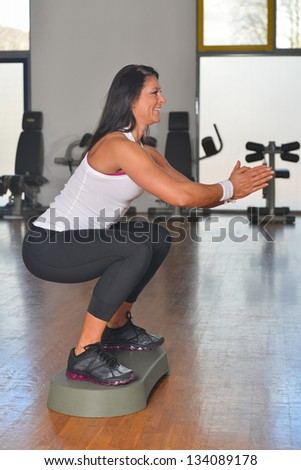 Happy fitness woman at aerobics class in gym