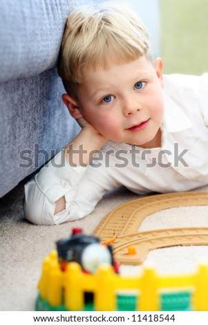 Happy five year old boy playing with his train set