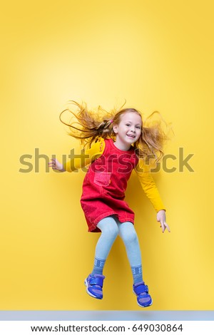 Shutterstock Happy five year old girl in bright summer clothes jumping for joy over yellow background. Happy childhood. Copy space.