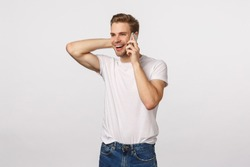 Happy flattered and pleased handsome blond guy receive praises or good news via phone call, holding smartphone near ear, touching neck silly and embarassed, standing white background