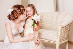 Happy flower girl gives a flower to bride. Wedding. Just married. Wedding hairstyle