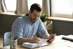 Happy focused young 30s businessman holding smartphone in hands, writing notes in personal daily planner, planning workday, checking schedule or handwriting important information at home office.