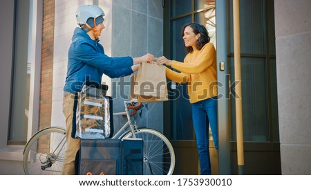 Happy Food Delivery Man Wearing Thermal Backpack on a Bike Delivers Restaurant Order to a Beautiful Female Customer. Courier Delivers Takeaway Lunch to Gorgeous Girl in Urban Building.
