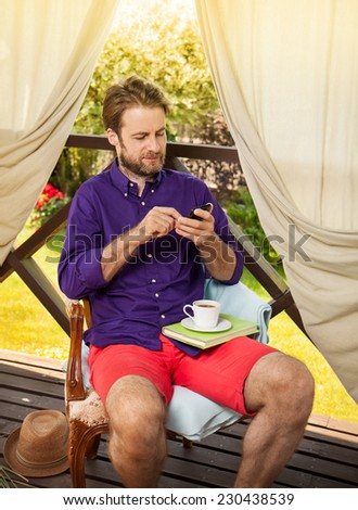 Happy forty years old caucasian man looking at mobile phone outdoor on garden terrace during sunny summer day. Countryside weekend or holiday concept.