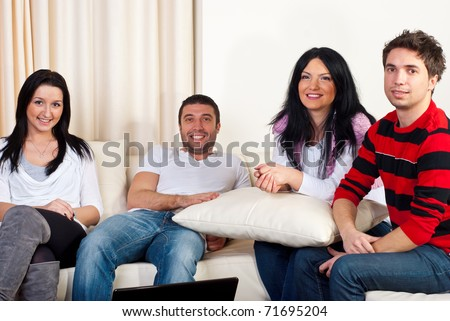 Happy four friends having a meeting in a house and sitting together on couch