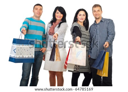 Happy four friends holding and showing their shopping bags isolated on white background