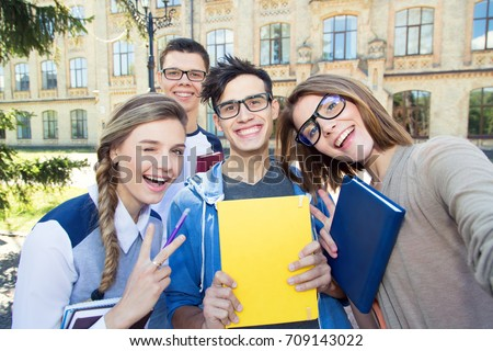 Happy four student friends. Cheerful self photo of a group of students on a university campus background.