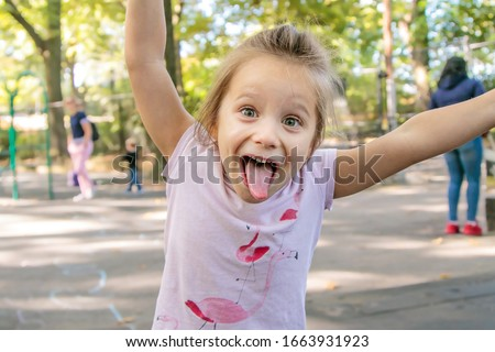Happy four year old girl making a silly face with a stuck out tongue while playing on a playground. Stock photo ©