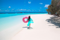 Happy free woman walking with pink Inflatable donut float. Summer Vacation. Girl wearing Chiffon Beach Dress enjoying exotic beach by turquoise water seaside. Maldives island paradise background.