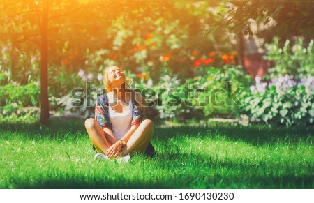 Happy free young woman sitting outdoors in yoga position with closed eyes on summer park grass Calm girl enjoy smile and relax in spring city air. Mindset inner light peace concept.