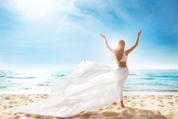 Happy Freedom Woman on Beach Enjoying Sun Arms Outstretched. Rear View of Girl Raised Hands fluttering White Dress on Wind. Summer Holiday Tropical Travel. Carefree Relax