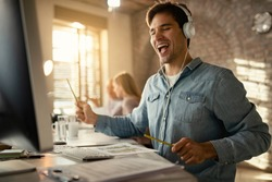 Happy freelance worker having fun while working at office desk and listening music over headphones. His colleagues are in the background.
